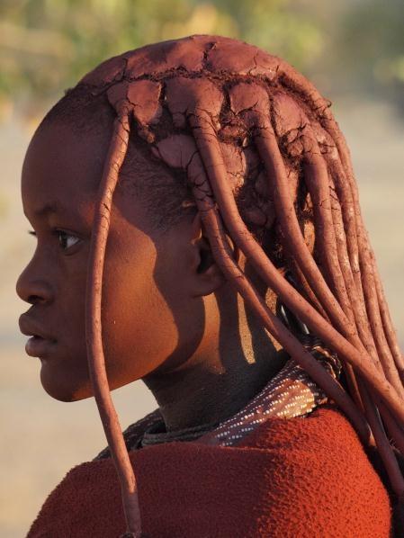 Покрытие волос и всего тела специальной смесью из охры, жира, пепла. Женщина народа «Химба», Намибия
